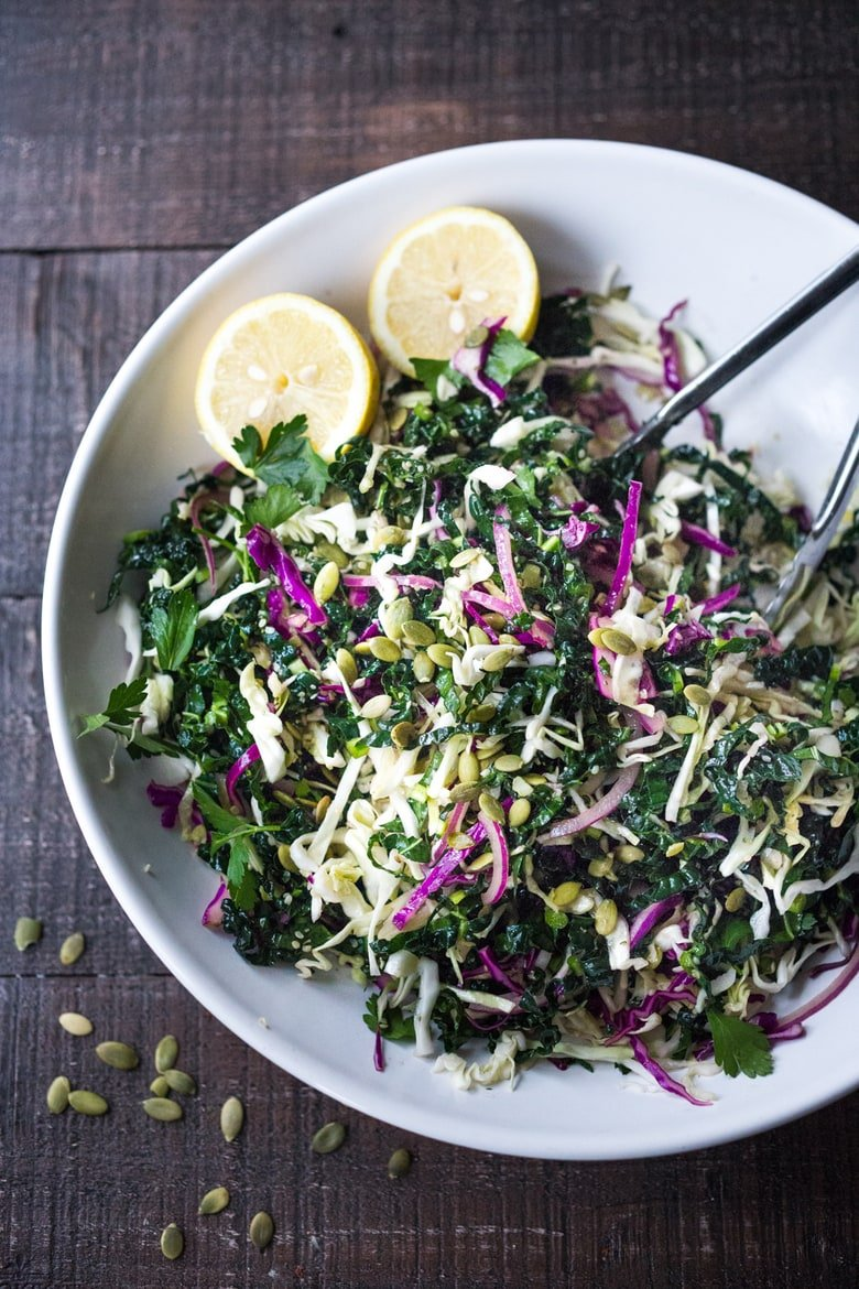Everyday Kale Salad with simple Lemon Dressing can be made ahead, then used DAILY to top off tacos, wraps, buddha bowls, burgers, and even pizza during the week! Vegan and Gluten Free, this amazing kale slaw keeps for up to five days in the fridge. Meal Prep Savior! #kale #kalesalad #kaleslaw #mealprep #everydaysalad #kale #simplesalad | www.feastingathome.com