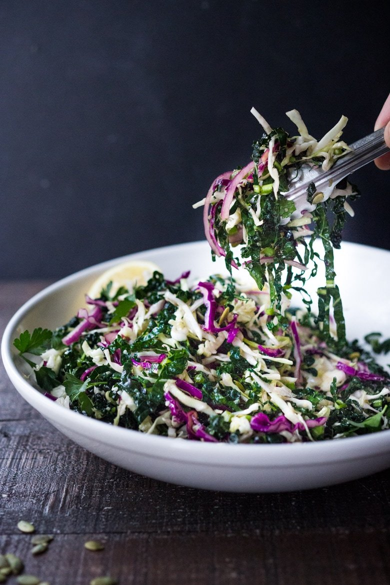 Everyday Kale Salad with simple Lemon Dressing can be made ahead, then used DAILY to top off tacos, wraps, buddha bowls, burgers, and even pizzaduring the week! Vegan and Gluten Free, thisamazingkale slaw keeps for up to five days in thefridge. Meal Prep Savior! #kale #kalesalad #kaleslaw #mealprep #everydaysalad #kale #simplesalad | www.feastingathome.com