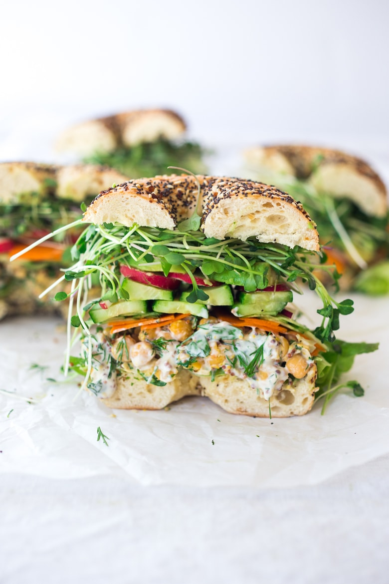 This Herby Chickpea Salad Sandwich is made with a flavorful smashed chickpea salad loaded up with lots of herbs, and layered with crunchy carrots & radishes, cucumber, avocado and sprouts. Vegan and Gluten-free adaptable! #greengoddess #greengodesssandwich #bagelsandwich #chickpeasalad #vegan