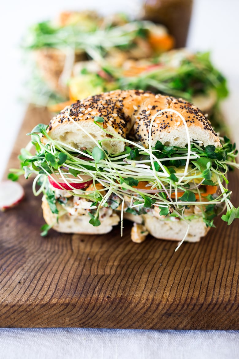 20 Healthy Chickpea Recipes! || This Herby Chickpea Salad Sandwich is made with a flavorful smashed chickpea salad loaded up with lots of herbs, and layered with crunchy carrots & radishes, cucumber, avocado and sprouts. Vegan and Gluten-free adaptable! #greengoddess #greengodesssandwich #bagelsandwich #chickpeasalad #vegan