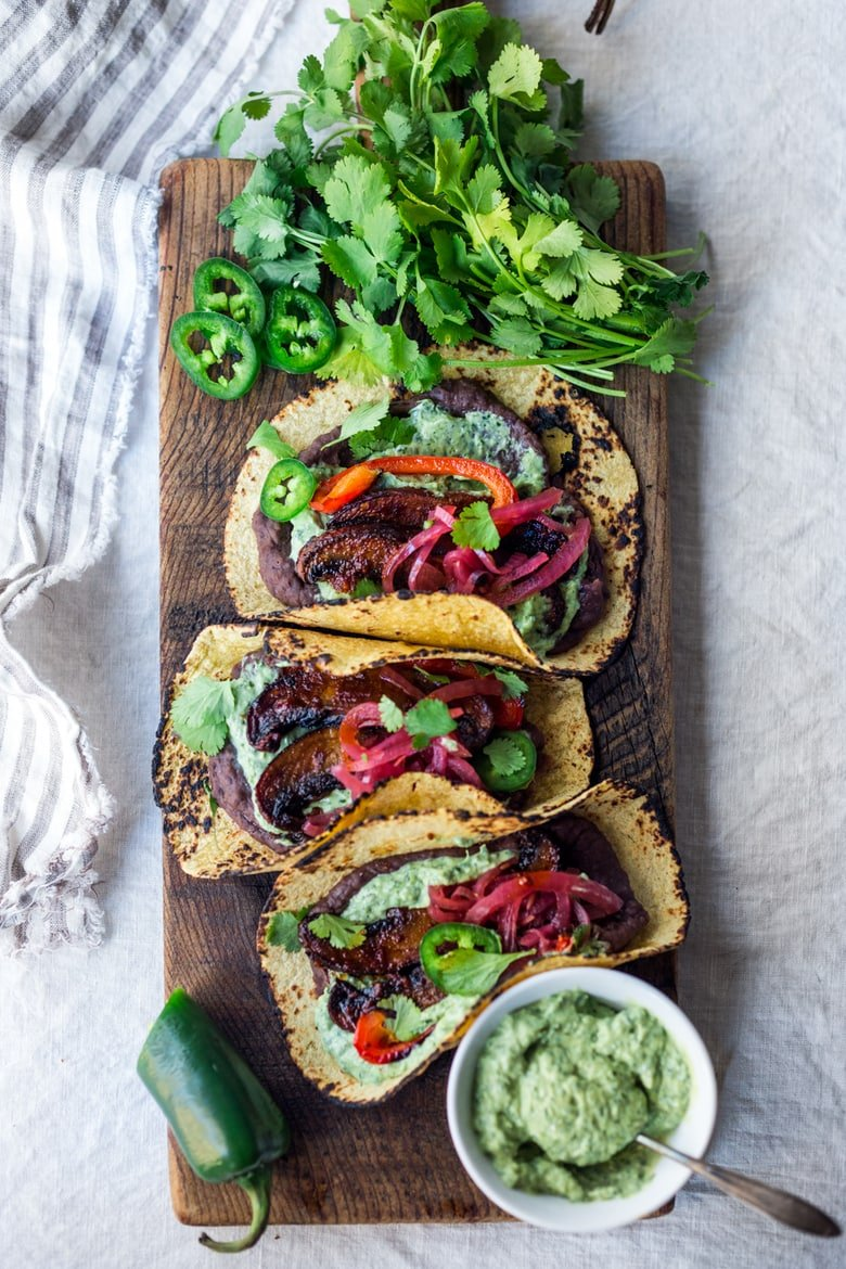Chipotle Portobello Tacos on a wood board with Vegan Cilantro Crema