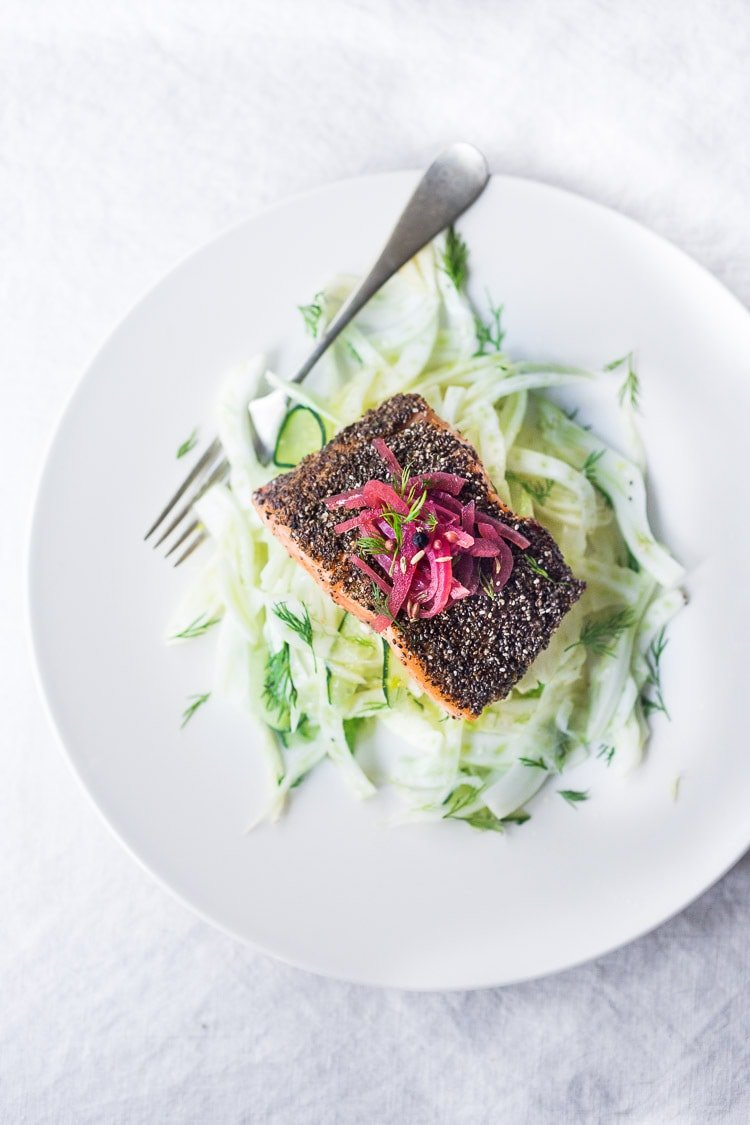 Chia Crusted Salmon, served over cool crunchy fennel slaw, topped with quick pickled onions. A simple, elegant dinner that is quick and healthy. #salmon #fennel #chia #fennelslaw #fennelsalad