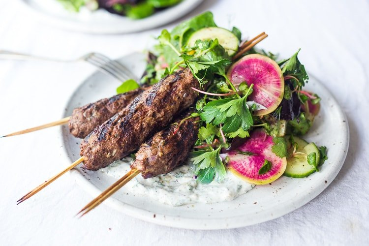 Grilled Lamb Kebabs with a tangy Herb Salad and Dilled Yogurt Sauce- a delicious, healthy, paleo friendly recipe featuring ground lamb spiced with Middle Eastern seasonings. #lambkebabs #americanlamb #groundlamb #lamb #feastingathome #herbsalad #yogurtsauce