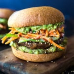 This Asian-style, grilled, vegan portobello mushroom burger is full of delicious umami flavor! It's lathered with Asian-style Guacamole, topped with a cool cucumber ribbon salad and crunchy carrot slaw. Healthy, delicious and really satisfying. AND totally vegan! #veganburger #portobelloburger #veganportobelloburger #portobellomushroomrecipes #portobello #vegan #veganburger #grilled #grilledportobello