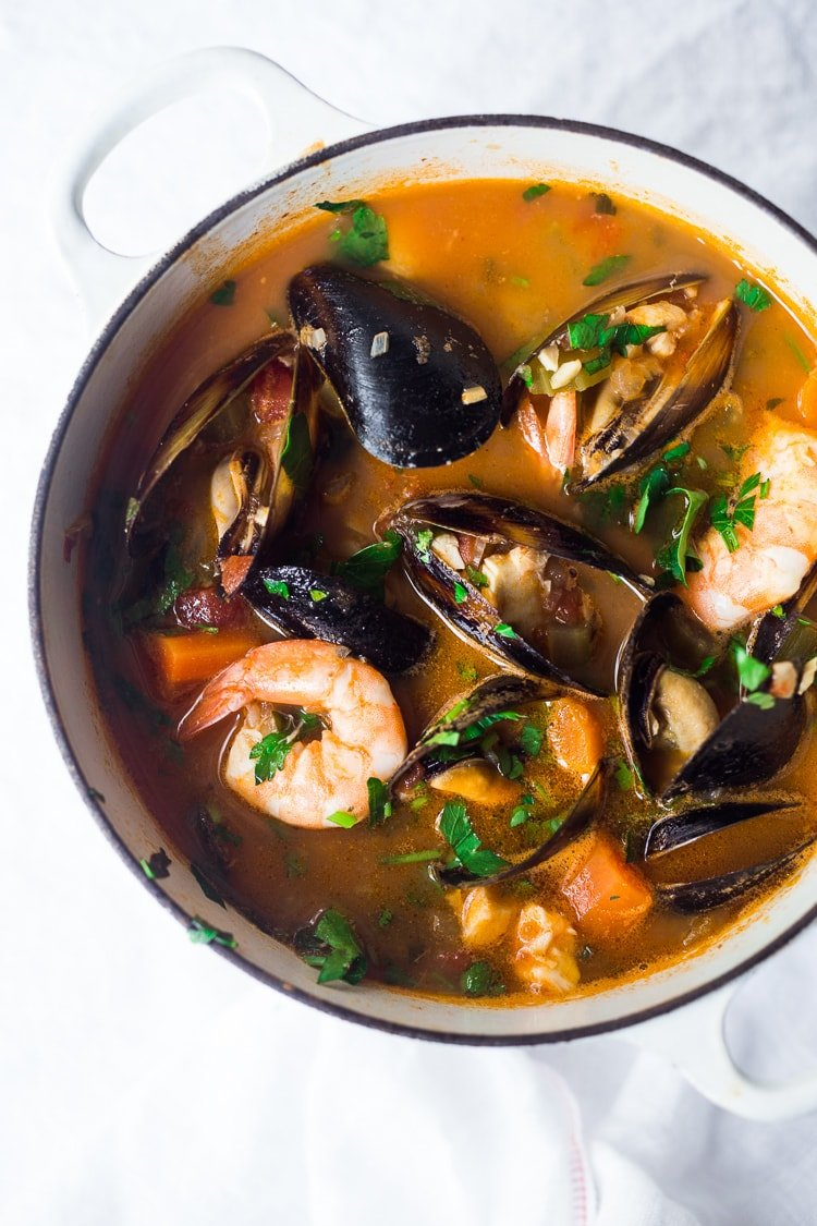 A simple authentic Cioppino Recipe that is easy to make and full of flavor. Fresh fish and seafood in a flavorful light broth. Serve with crusty bread to mop up all the juices. #cioppino #seafoodstew #fishstew #fishermansstew #italianstew #cioppinorecipe