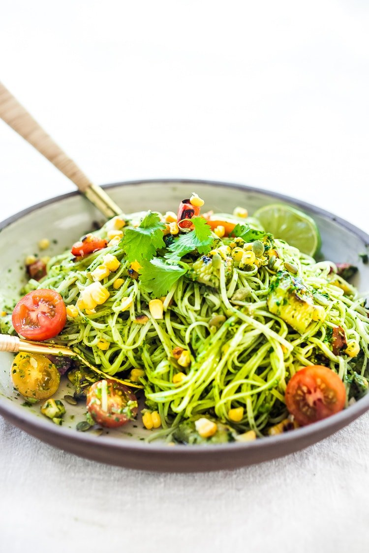 This Corn and Zucchini Pasta Salad is made with gluten-free rice noodles and loaded up with grilled summer veggies, then tossed in the most flavorful Cilantro Pesto.... deliciously addicting! Vegan and Gluten-free! #summerpastasalad #pastasalad #cornpasta #cilantropesto #zucchinipasta #zucchini #potluck