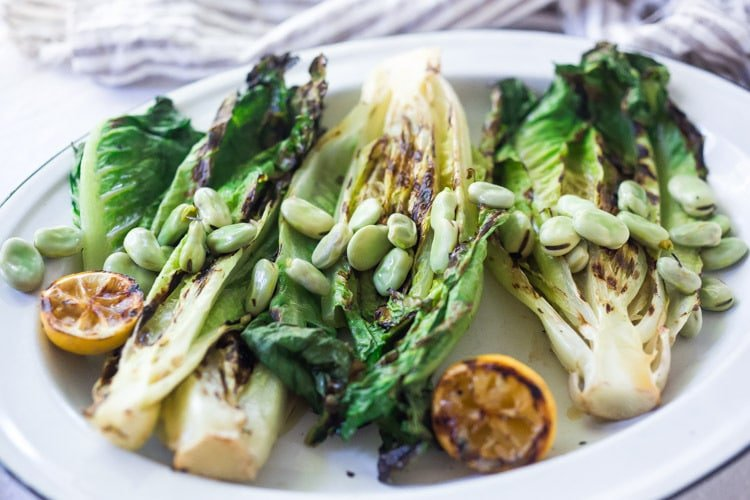 Healthy delicious, Grilled Romaine Salad with Corn, Fava Beans and Avocado - a light and refreshing summer meal. Keep it vegan or add grilled shrimp for added protein. Either way, it's sure to be your new favorite salad. Don't have access to fresh Fava beans? No worries, sub edamame! #grilledromaine #salad #romaine #fava #avocado #grilled #vegan