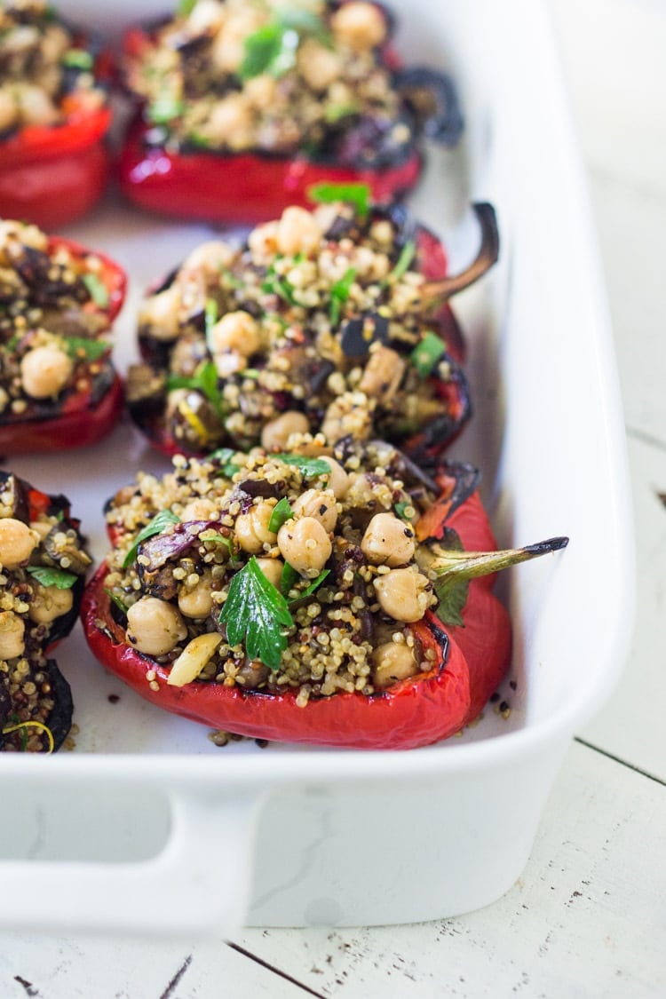 These healthy, vegetarian Stuffed Peppers with Quinoa, Eggplant, Chickpeas, Zaatar Spice and Zhoug Yogurt are the perfect make-ahead meal for summer gatherings and potlucks. Or meal prep them on Sunday to serve up during the busy workweek! Gluten free and Vegan adaptable! #stuffedpeppers | Feasting at Home