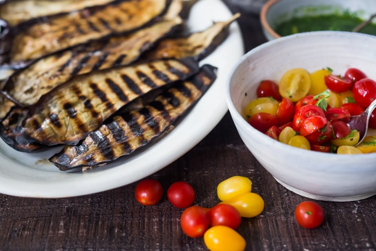 Grilled Eggplant Steaks with Fresh Tomato Relish and an Italian herb sauce called Gremolata. Keep it vegan or add crumbled cheese. A simple, healthy dinner recipe! #eggplant Feastingathome #grilledeggplant #gremolata #eggplantsteaks #eggplantrecipes #eggplantsteaks #healthydinner #meatlessdinner #vegan