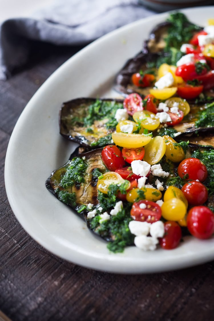 Grilled Eggplant Steaks with Fresh Tomato Relish and an Italian herb sauce called Gremolata. Keep it vegan or add crumbled cheese. A simple, healthy dinner recipe! #eggplant Feastingathome #grilledeggplant #gremolata #eggplantrecipes #eggplantsteaks #healthydinner #meatlessdinner #vegan
