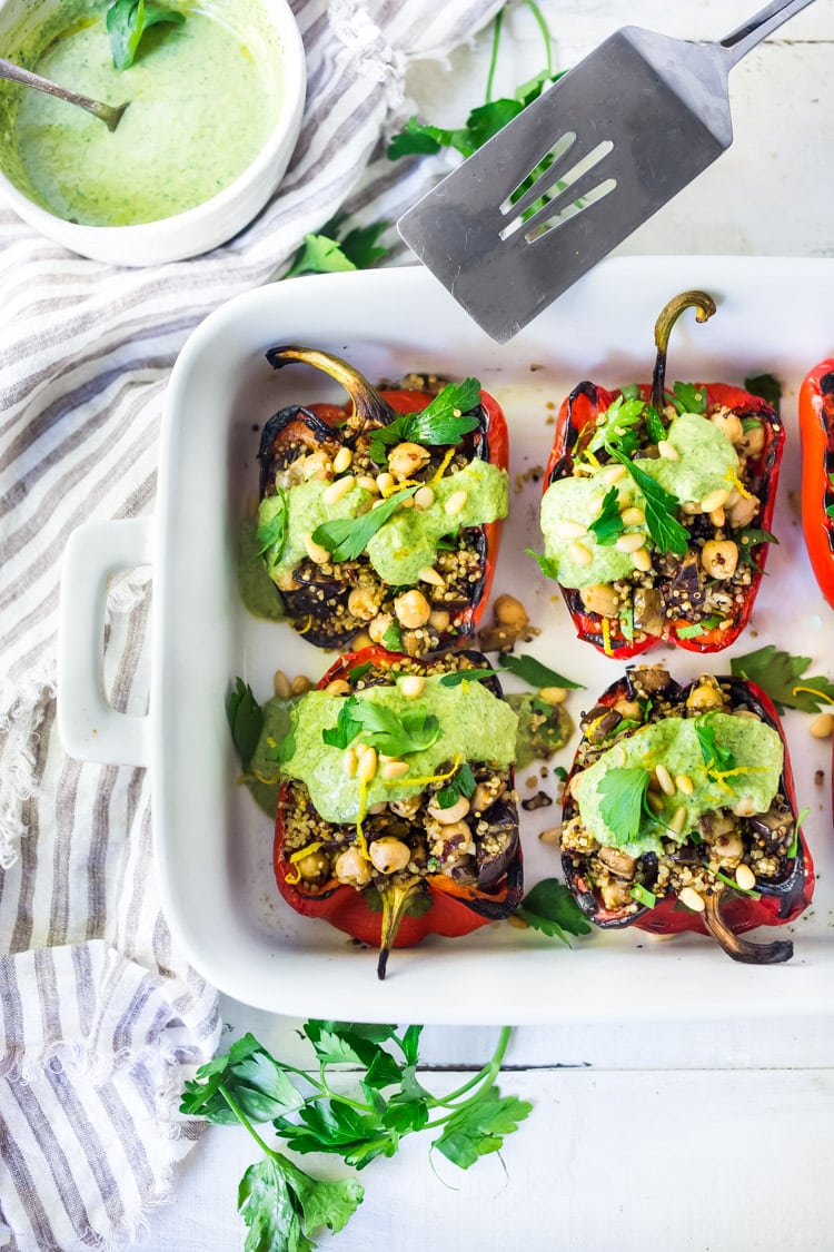Middle Eastern Stuffed Peppers with Quinoa, Eggplant, Chickpeas and Zhoug Yogurt are the perfect make-ahead meal for summer gatherings and potlucks. Or meal prep them on Sunday to serve up during the busy workweek! Gluten-free, healthy and Vegan adaptable! #stuffedpeppers #zhoug