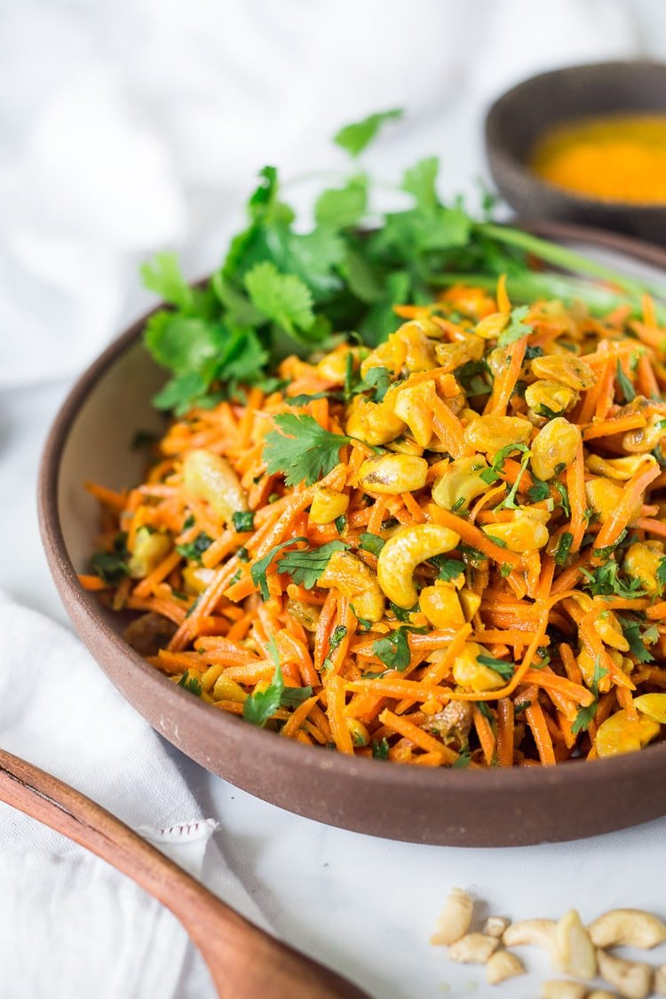 Bombay Carrot Salad with cashews and raisins, tossed in a fragrant Indian Curry dressing. Healthy and vegan this carrot salad recipe is so EASY to make, and can be made-ahead. #carrotsalad #carrotslaw #vegan #indiancarrotsalad #recipe #carrotsaladrecipe