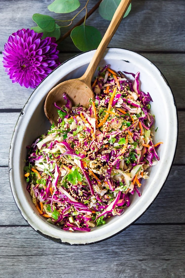 Easy Crunchy Asian Slaw- a simple vegan slaw with the BEST SLAW DRESSING EVER that can be made ahead! Serve this alongside fish, tofu, or chicken or stuffed into tacos, topped onto burgers, or added to buddha bowls. A great way to add more veggies into your everyday meals. #slaw #asianslaw #veganslaw #easyslaw #tacoslaw