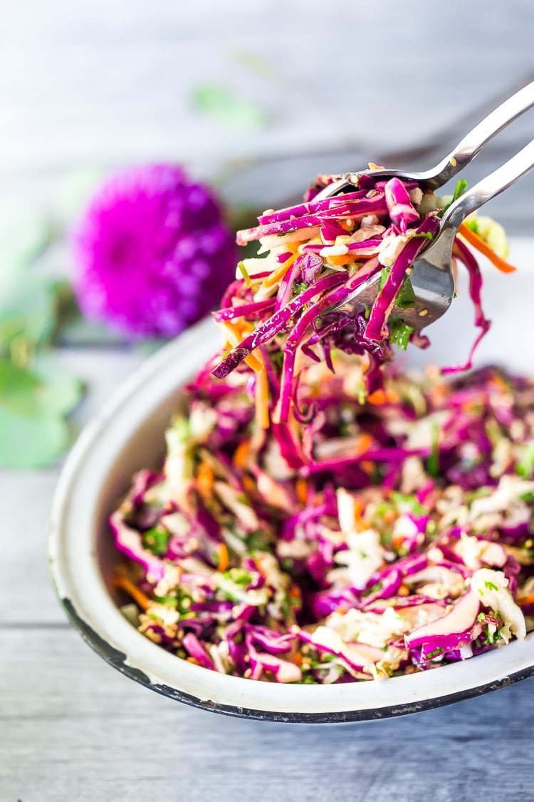 Easy Crunchy Asian Slaw- a simple vegan slaw with the BEST SLAW DRESSING EVER that can be made ahead! Serve this alongside fish, tofu, or chicken or stuffed into tacos, topped onto burgers, or added to buddha bowls. A great way to add more veggies into your everyday meals.#slaw #asianslaw #veganslaw #easyslaw #tacoslaw