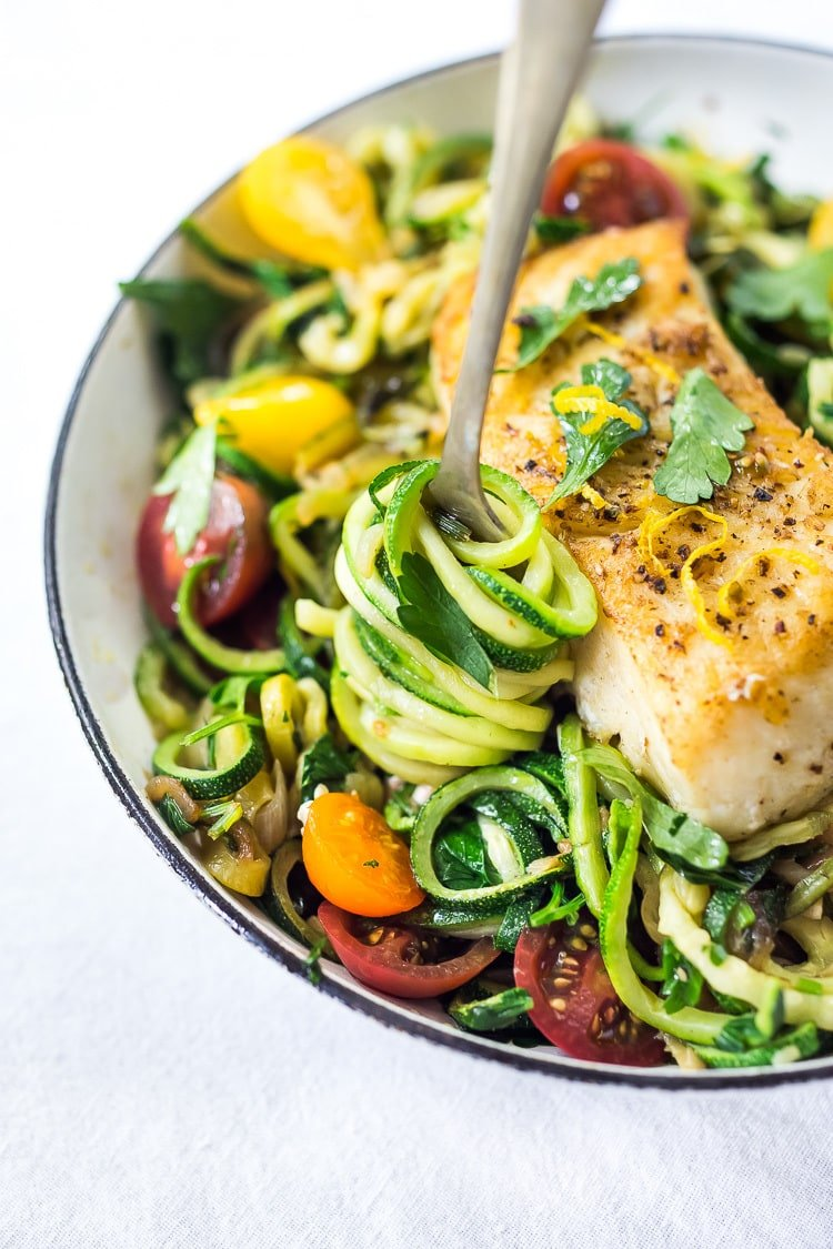 A simple, healthy Halibut recipe served over Lemony Zucchini Noodles with olive oil, garlic and parsley, topped with sweet summer tomatoes. A quick and easy low-carb meal! #keto #zucchininoodles #zoodles #halibut #halibutrecipes #lowcarb #healthy