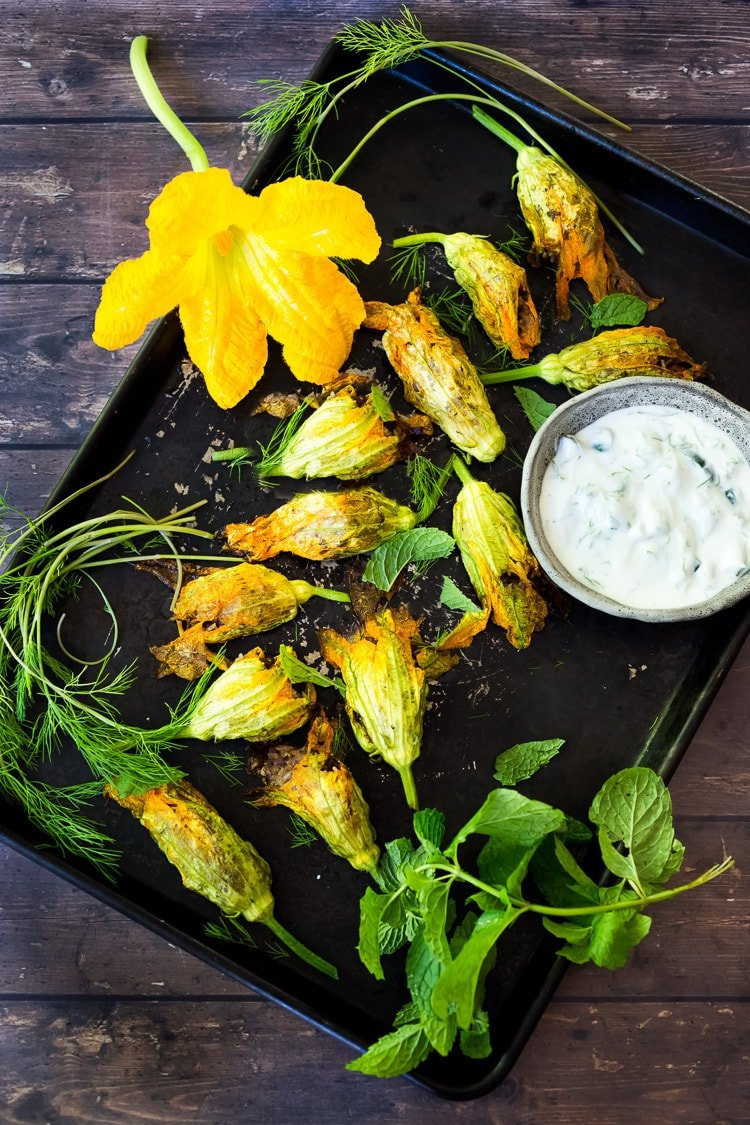 Stuffed Squash Blossoms are filled with lamb and rice and served with tzatziki. A light and healthy summer meal!