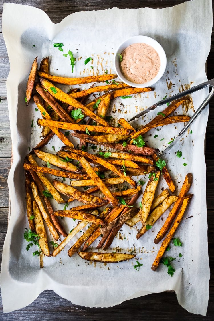 CrispyBaked Sweet Potato Fries - Healthy, EASY and oh so crispy! A delicious vegan side that is good for you and full of amazing flavor! Vegan and Gluten-free. #sweetpotato #sweetpotatofries #baked #vegan #bakedsweetpotato #harissa