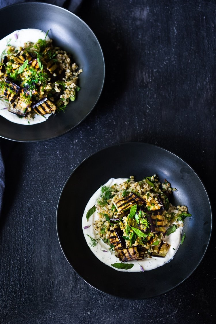 Grilled Eggplant Salad with Freekeh. Loaded up with fresh herbs and served over a tangy yogurt dressing, this healthy salad is full of Middle Eastern flavor. Vegan adaptable #freekah #eggplantsalad #freekehsalad #freekehrecipe #vegetarian #vegan #healthysalad