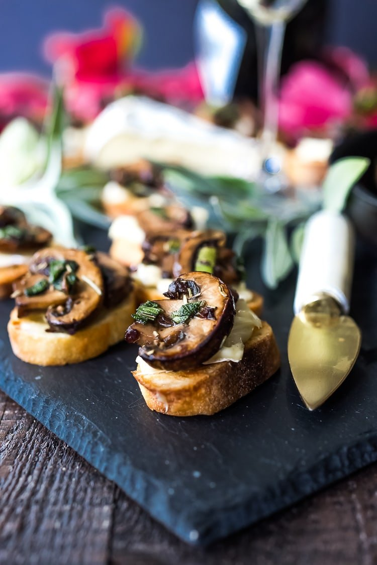 Mushroom Bruschetta with Triple Cream Brie, Sage and Truffle Oil - a surprisingly easy appetizer that tastes amazing and looks elegant! Perfect for holiday gatherings. #mushroombruschetta #mushroomappetizer #appetizer #holidayparty #holidayappetizer #veganbruschetta #glutenfreebruschetta #veganmushroombruschetta #truffleoil #brieappetizer #christmasappetizer