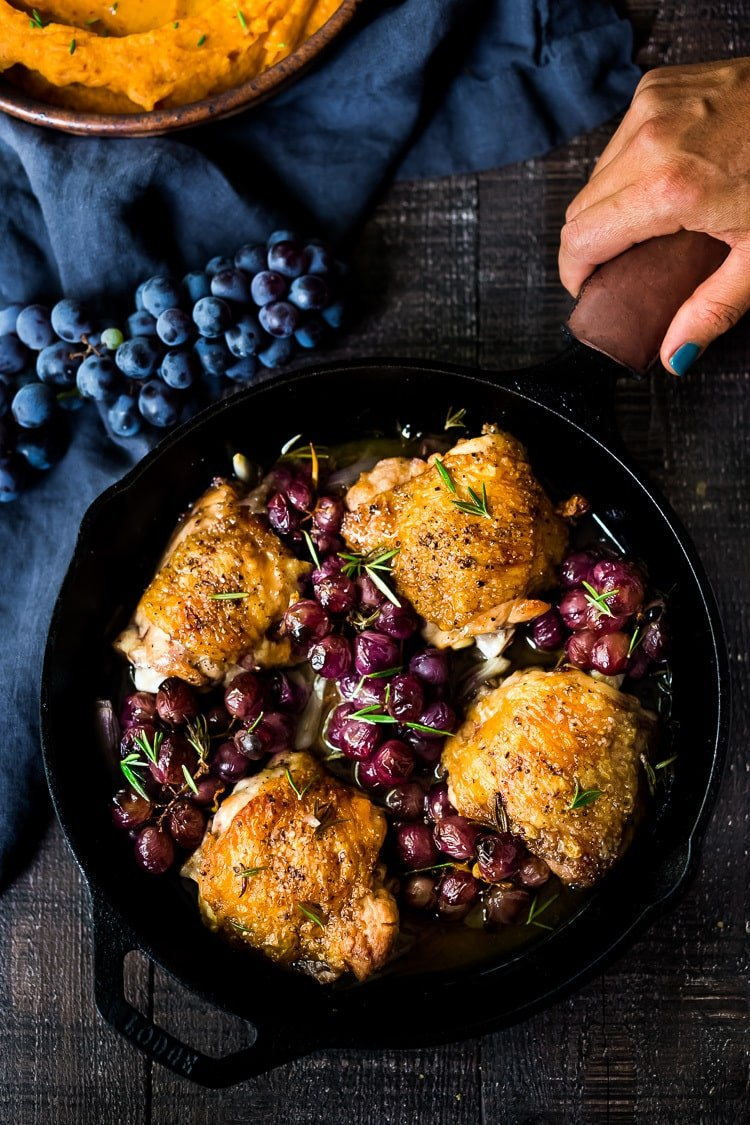 Rosemary Chicken Thighs with Roasted Grapes and Shallots, served over Whipped Ginger Sweet Potatoes - a simple, easy, fall-inspired skillet dinner that can be made in 30 minutes!  #rosemarychicken #skilletchicken #bakedchicken #roastedgrapes #chicken #chickenthighs