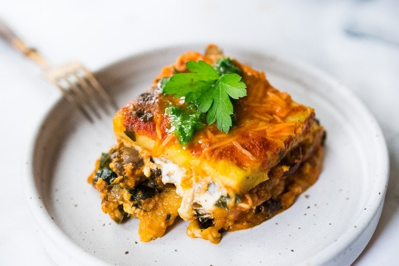 Polenta Lasagna with Roasted Red Pepper Sauce - an easy, vegan adaptable main dish that is perfect for the holiday table. Gluten-free! #veganthanksgiving #polentalasagna #veganlasagna #vegetarianmaindish #veganchristmas #polenta #lasagnarecipes #glutenfreelasagna