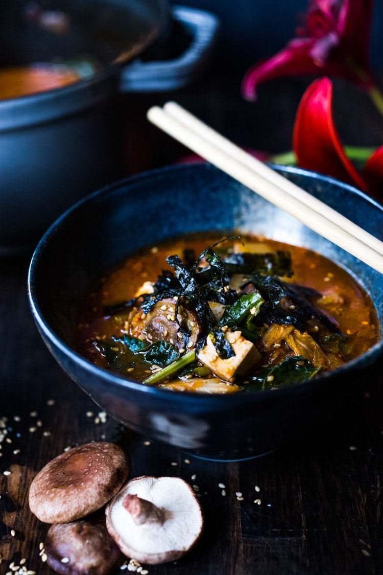 A simple easy recipe for Kimchi Soup- this version is vegan, made with shiitake mushrooms, silken tofu and kale. Serve over rice or noodles! Delicious Korean flavor! #kimchisoup #easykimchisoup #vegankimchisoup #plantbased #cleaneating #eatclean #vegansoup #koreansoup