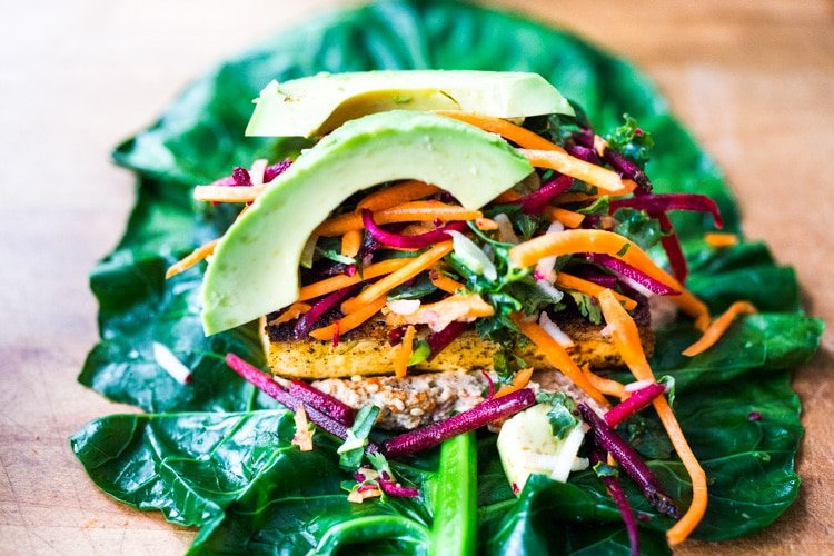 Rainbow Wraps! This vegan collard greens wraps are filled with hummus, crispy tofu, shredded beets, carrots and avocado! Drizzle with Tahini sauce! A delicious healthy lunch! #eatclean #cleaneating #vegan #veganlunch #rainbowwrap #Wraps #veganwrap #plantbased #collardgreens