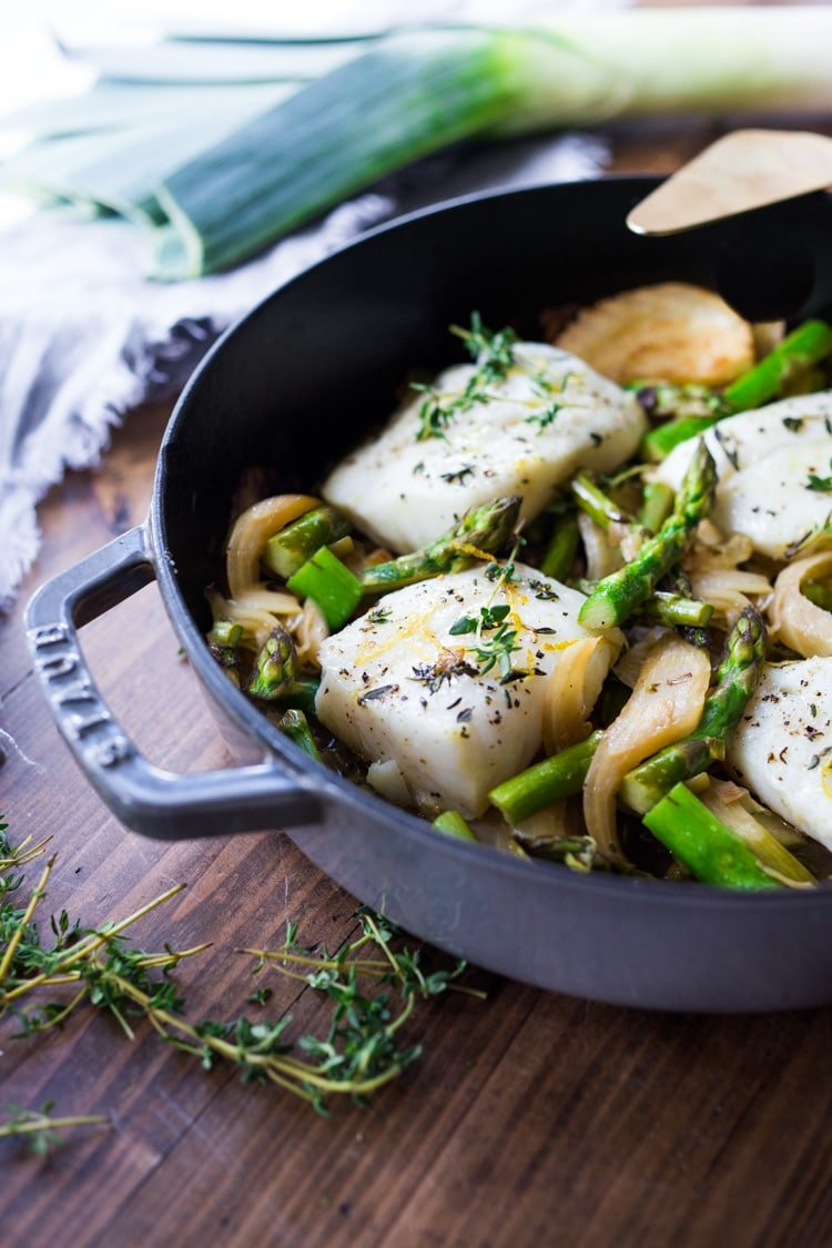 Healthy delicious Baked Cod Recipe with lemon, garlic and thyme, nestled in Spring vegetables- Asparagus, Fennel and Leeks. Simple & Easy. #cod #codrecipe