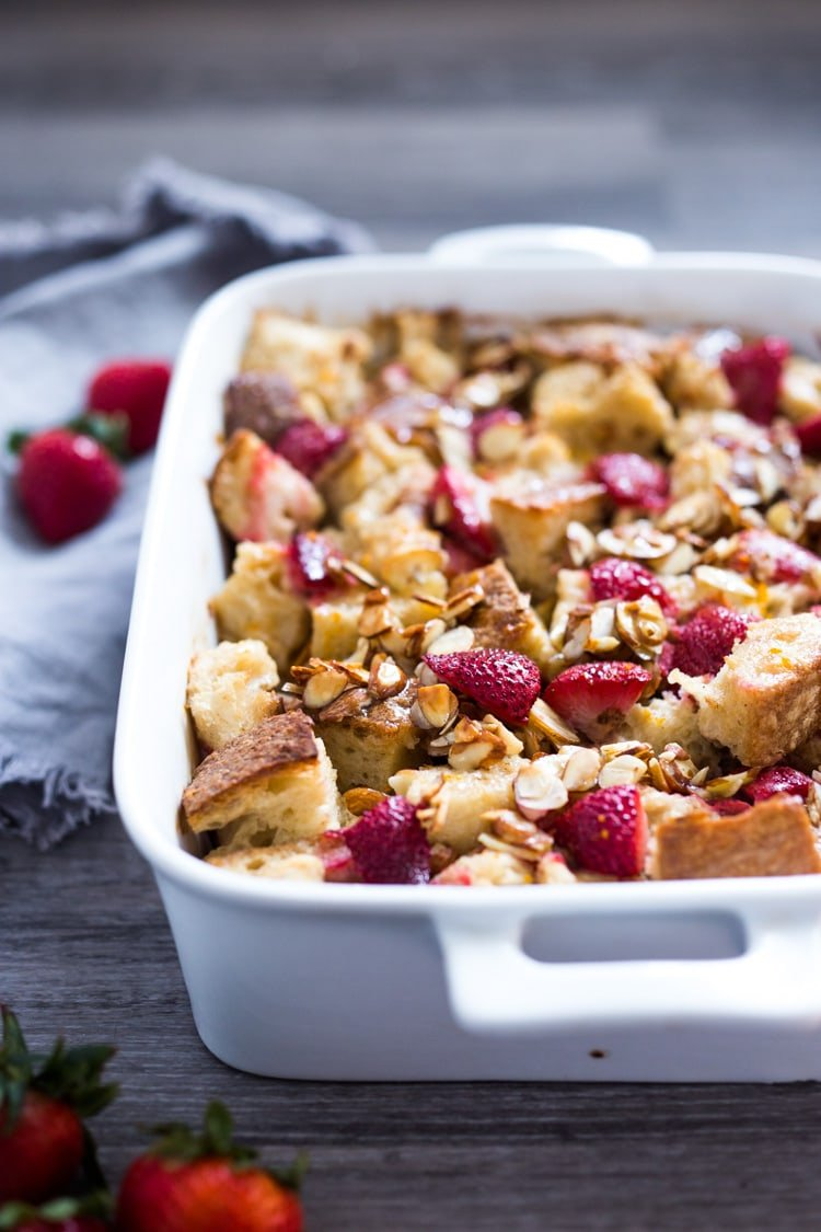 Baked French Toast (Vegan) with silken tofu, fresh berries orange zest and almonds. A healthy version of our favorite brunch recipe! Can be made ahead! #brunch #mothersday #veganbrunch #vegan #frenchtoast #feastingathome #healthybreakfast