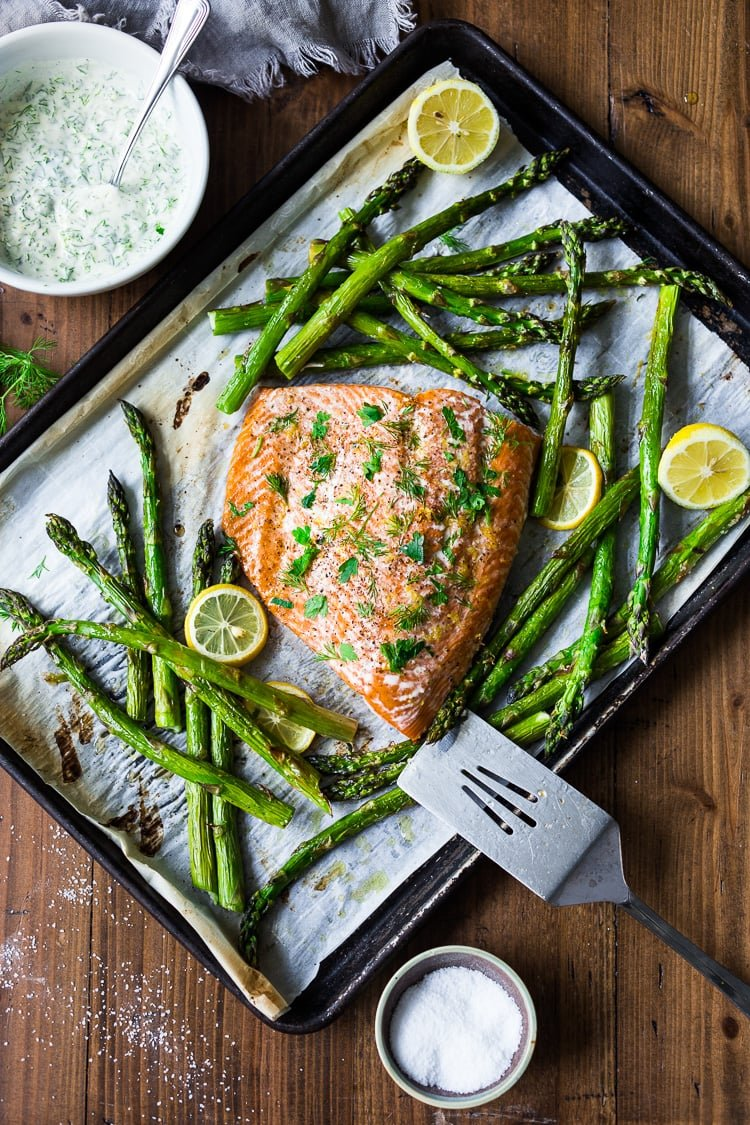 Simple Baked Salmon with Asparagus and Yogurt Dill Sauce - an EASY healthy, sheet-pan dinner that comes together in under 30 minutes. #salmon #roastedsalmon #bakedsalmon #aspargus #dinner #sheetpandinner #easyrecipes #healthy #keto #lowcarb