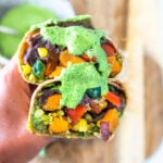 These Vegan Peruvian Burritos are filled with roasted sweet potato, fresh corn, peppers, quinoa and creamy blackbeans, then drizzled with spicy Peruvian Green Sauce. A flavor bomb! Vegan and Delicious! #vegan #burrito #peruvianfood #peruvianrecipes #veganburrito