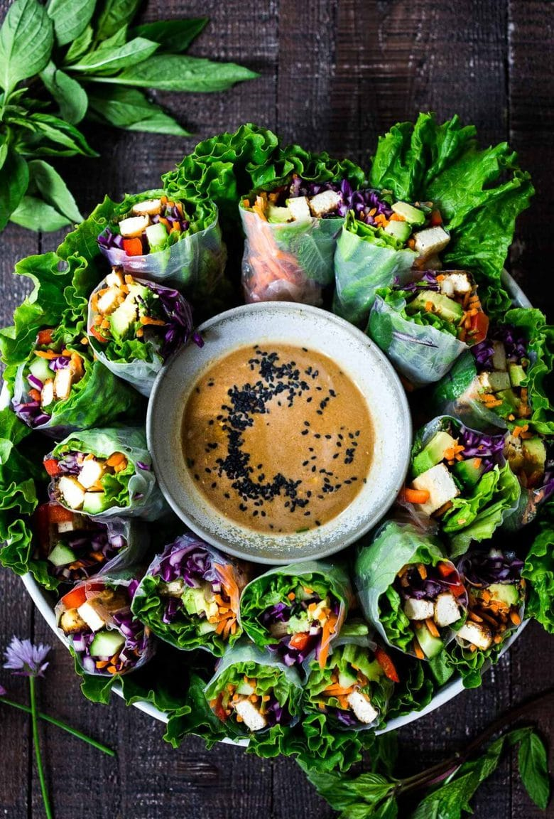 How to make fresh Spring Rolls with BEST EVER Peanut Sauce! These VEGAN spring rolls can made ahead and stored for healthy lunches or potlucks and gatherings. #springrolls #veganspringrolls #freshspringrolls #howtostorespringrolls #howtomakespringrolls
