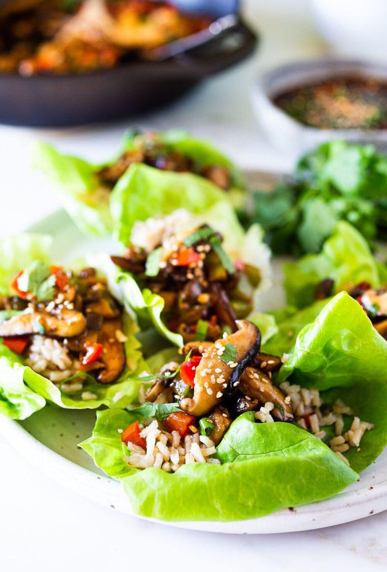 Delicious Vegan Lettuce Wraps are filled with Teriyaki Mushrooms and brown rice- a healthy delicious lunch or appetizer! #veganlunch #vegan #veganlettucewrap #shiitakewrap