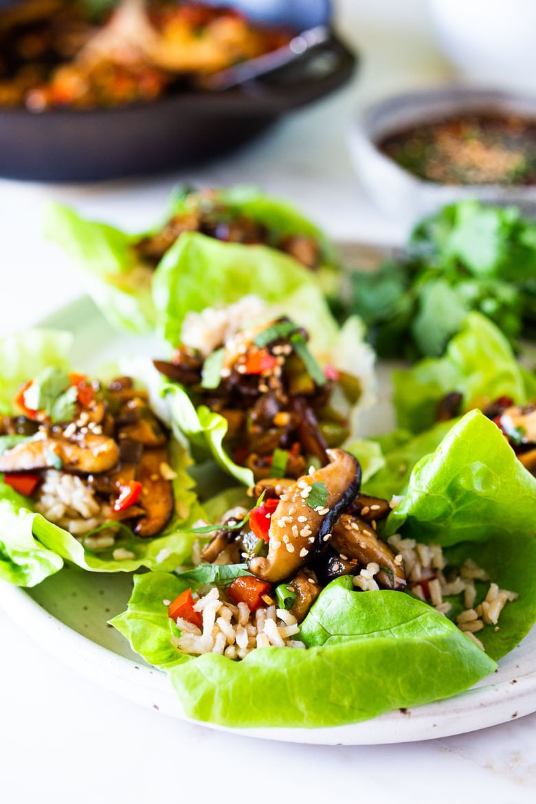 Delicious Vegan Lettuce Wraps are filled with Teriyaki Mushrooms and brown rice- a healthy delicious lunch or appetizer! #veganlunch #vegan #veganlettucewrap #shiitakewrap