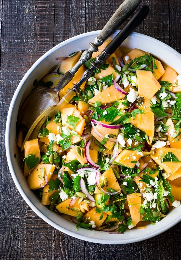 A refreshing Cantaloupe Salad with red onion, lime, cilantro, mint, Aleppo chili flakes, pepitas and optional crumbled feta (optional) - an easy healthy summer salad, perfect for potlucks and gatherings. Vegan adaptable! #cantaloupe #cantaloupesalad