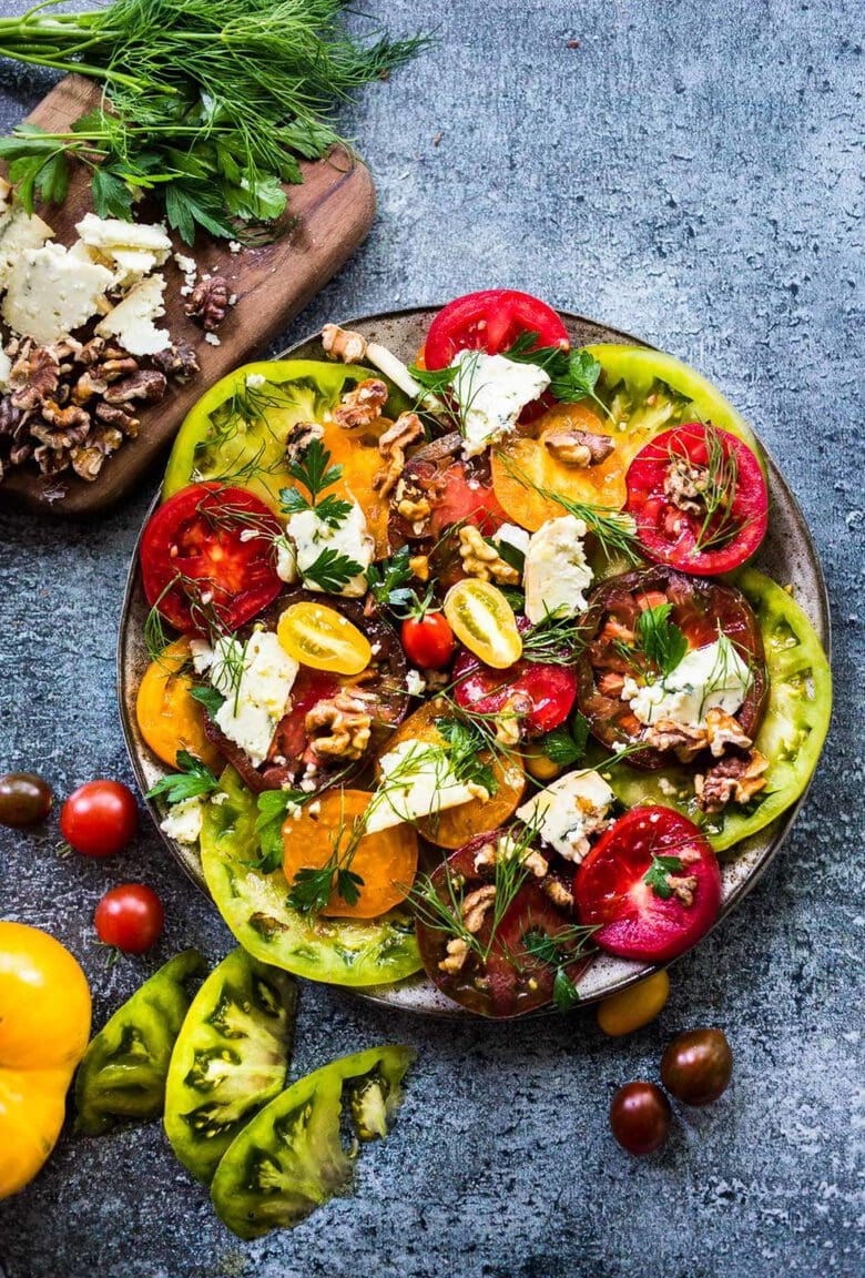 Heirloom Tomato Salad with Toasted Walnuts and Smoked Blue Cheese - a simple summer salad highlighting sweet and juicy heirloom tomatoes. Can be made in 15 minutes! #tomatosalad #tomatowalnutsalad #heirloomtomatosalad #summersalad #farmersmarketsalad #tomatorecipes #walnutsalad