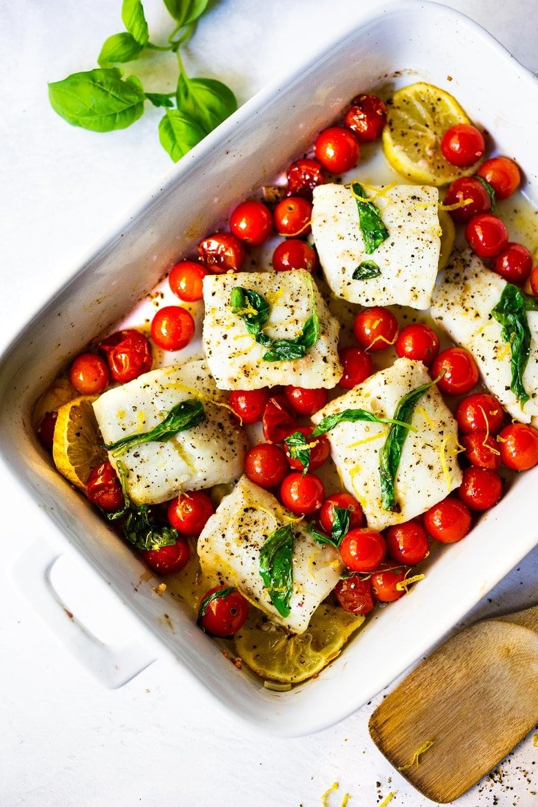 Simple Baked Cod with Tomatoes, Basil, Garlic Lemon- a fast and easy weeknight dinner that is healthy and delicious! #bakedcod #bakedfish #keto #keporecipes #weeknightdinner #weeknightdinners #easyfishrecipes