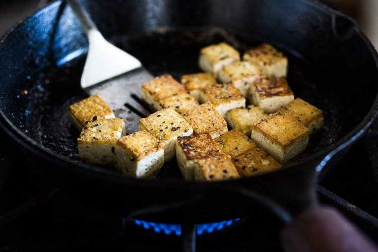 Here's a simple easy recipe for Crispy Tofu that can be made on the stovetop in 20 minutes with just 3 ingredients. You'll find a million uses for this crispy tofu and fun ways to season it - adding it to meals you are already making. #crispytofu #simpletofurecipes #easytofu #tofu #tofurecipes #friedtofu #stirfriedtofu