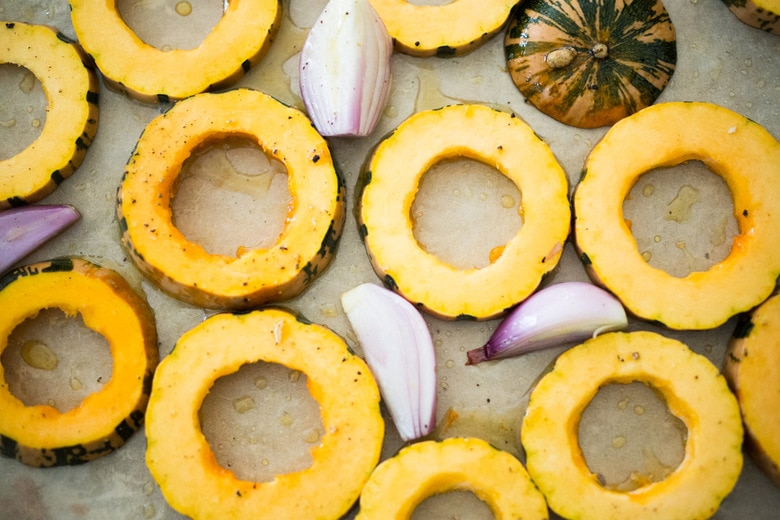 roasted delicata squash on a sheet pan in the oven