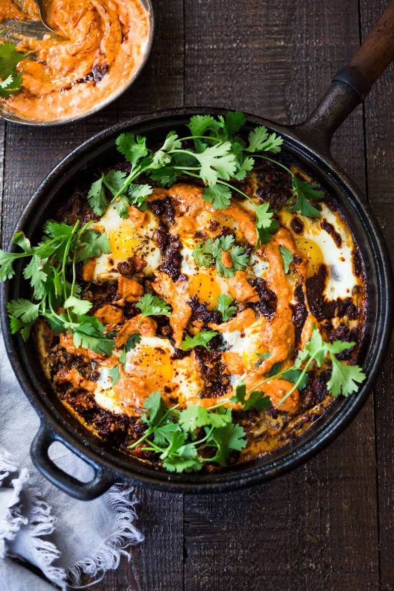 Moroccan Eggs! Eggs are baked in a flavorful lamb stew infused with Moroccan Spices, topped with Harissa Yogurt. A delicious breakfast or brunch recipe. #moroccanrecipes #bakedeggs #lambrecipes #groundlamb #brunch #breakfastrecipes
