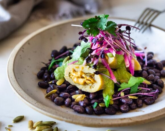 Butternut Tamales with flavorful Pumpkin Seed-Cilantro Sauce over a bed of seasoned black beans, topped with pickled onions and crunchy radishes! A flavorful vegetarian dinner. Vegan adaptable! Can be made ahead! #tamales #butternuttamales #vegantamales #vegetariandinner
