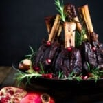 Oven Braised Lamb Shanks with Pomegranate - a festive, Moroccan-inspired lamb recipe that is elegant and delicious! Succulent lamb shanks are roasted in the oven until tender and falling off the bone then drizzled with a falvorful pomegranate sauce.  Serve over creamy soft polenta. #lambshanks #moroccanlamb #braisedlamb #lambrecipes #bakedlamb #lambrecipes #lamb