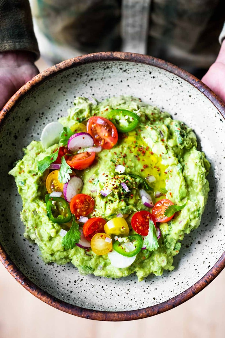 How to make the most delicious guacamole! A simple easy recipe for Guacamole that will be the hit of your party! A flavorful Mexican appetizer that is vegan, gluten-free and healthy. #guac #guacamole #guacamolerecipe #avocadodip