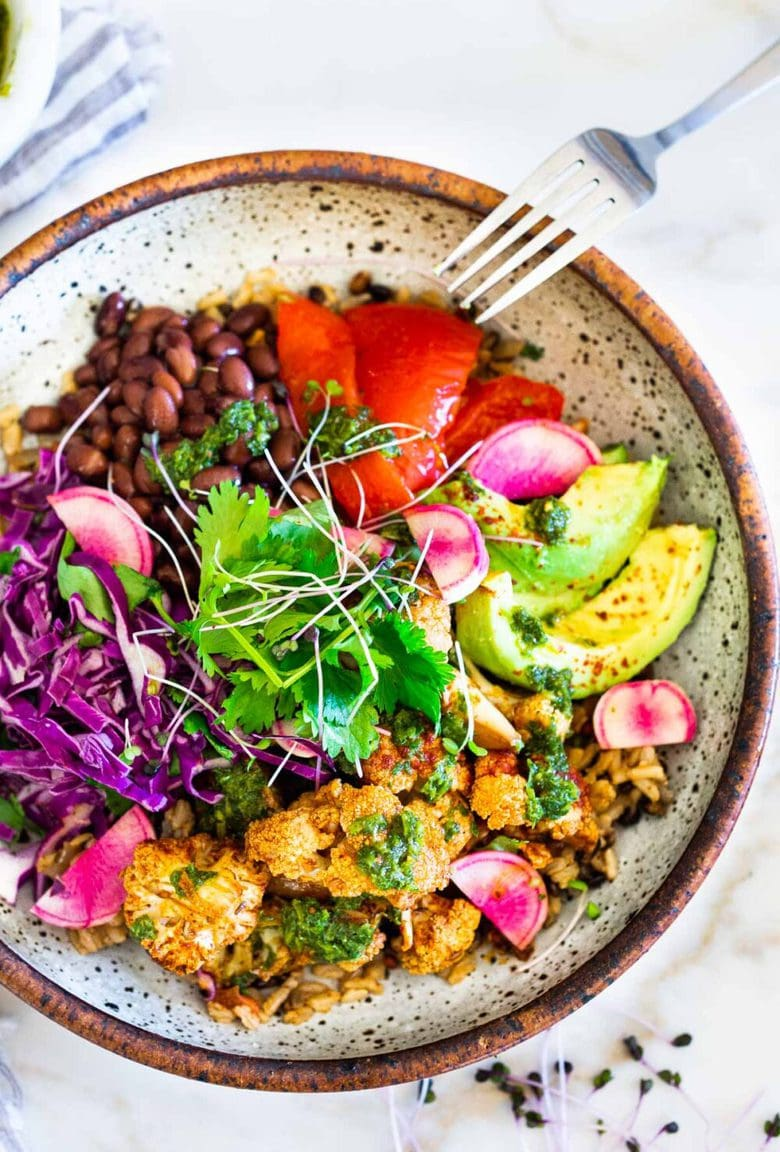 Smokey Cauliflower Chimichurri Bowls!  These filling vegan bowls are full of flavor and loaded up with healthy veggies. Served over seasoned black beans (and optional rice) with Mexican Slaw, radishes, avocado, cilantro and pickled onions. #roastedcauliflower #bowls #veganbowls #veganrecipes #buddhabowls #chimichurri #eatclean #cleaneating #plantbased #healthybowls