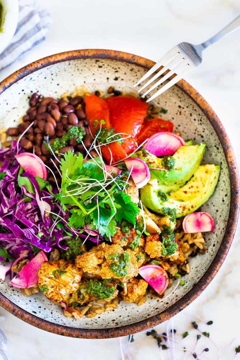 Our 20 BEST Buddha Bowls!|Smokey Cauliflower Chimichurri Bowls!  These filling vegan bowls are full of flavor and loaded up with healthy veggies. Served over seasoned black beans (and optional rice) with Mexican Slaw, radishes, avocado, cilantro and pickled onions. #roastedcauliflower #bowls #veganbowls #veganrecipes #buddhabowls #chimichurri #eatclean #cleaneating #plantbased #healthybowls