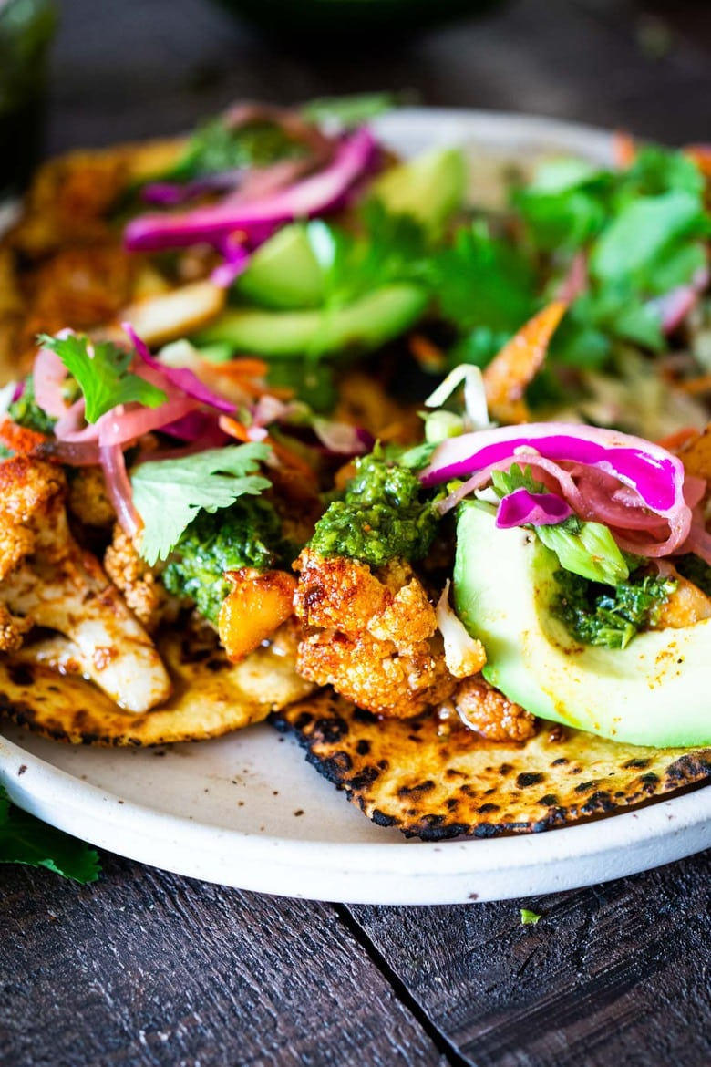 Smokey Cauliflower Chimichurri Tacos!  These filling vegan tacos are full of flavor and loaded up with healthy veggies. Served over seasoned black beans (and optional rice) with Mexican Slaw, radishes, avocado, cilantro and pickled onions. #roastedcauliflower #bowls #veganbowls #veganrecipes #buddhabowls #chimichurri #eatclean #cleaneating #plantbased #healthybowls