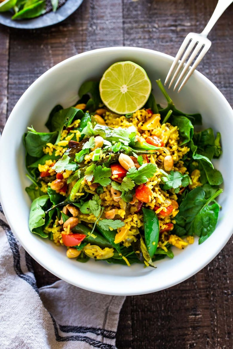 This fragrant, turmeric-infused, Indian Fried Rice is full of healthy veggies and can be made in under 30 minutes. Vegetarian, Gluten-free and Vegan adaptable, it is a fast and easy weeknight meal- great for using up leftover rice and veggies in the fridge.  #turmericrice #veggierice #friedrice #vegandinner