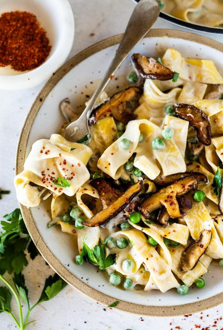Vegan Alfredo for two, tossed in a delicious cashew (or hemp) cream, with sauteed mushrooms, Meyer lemon zest and a secret ingredient that gives this extra complexity and depth. Can be made in under 30 minutes! #veganalfredo #veganalfredosauce