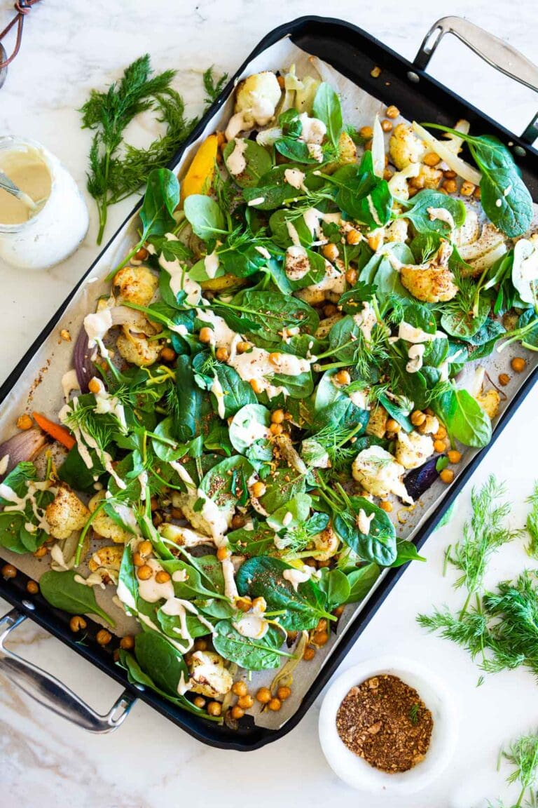 "Warm Winter Salad - a hearty ""entree"" salad made on a sheet pan with roasted cauliflower, carrots, fennel and chickpeas, topped with wilting spinach, drizzled with Everyday Tahini Sauce and sprinkled with fresh dill and Egyptian Dukkah. Vegan and Gluten-free. #sheetpandinner #warmsalad #vegansalad #sheetpanmeal #wintersalad #spinachsalad #cauliflowersalad"
