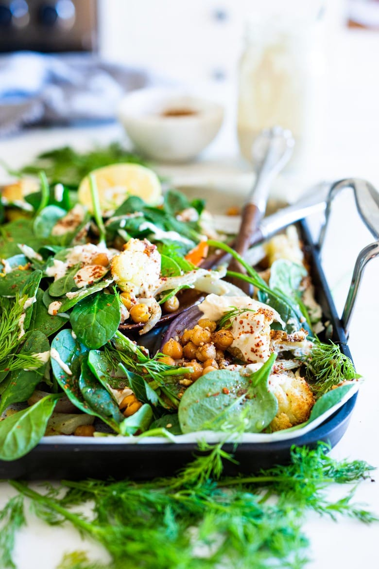 Warm Winter Salad - a hearty, Middle Eastern salad made on a sheet pan with roasted cauliflower, carrots, fennel and chickpeas, topped with wilting spinach, drizzled with Everyday Tahini Sauce and sprinkled with fresh dill and Dukkah. Vegan and Gluten-free. #sheetpandinner #warmsalad #vegansalad #sheetpanmeal #wintersalad #spinachsalad #cauliflowersalad #wintersalad #warmsalad